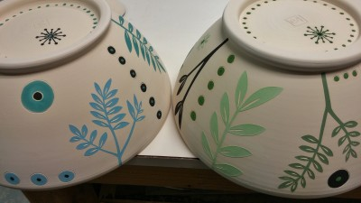 2 ceramic bowls with abstracted plant designs at rest in the studio